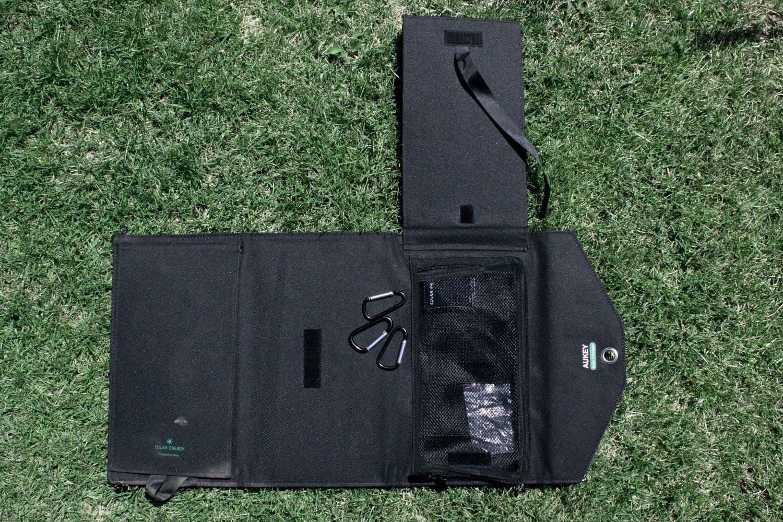 Die USB-Stecker befinden sich hinter einem kleinen Netz, in welchem auch das Handy oder Tablet verstaut werden kann.