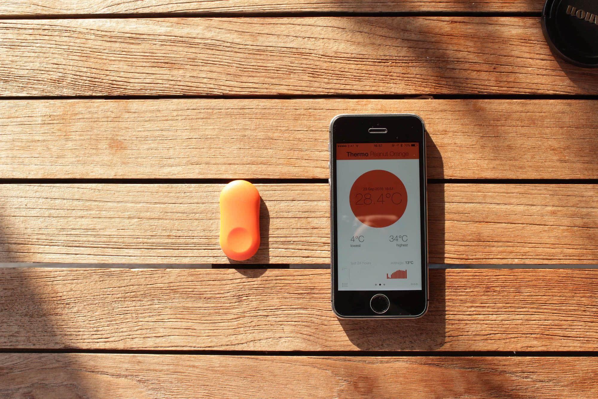Neben einem iPhone 5s ist zu sehen, wie klein das Thermometer ist.